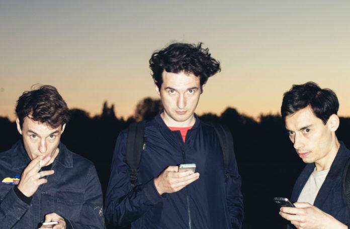 Trzech chłopaków ubranych na ciemno w tle zachód słońca