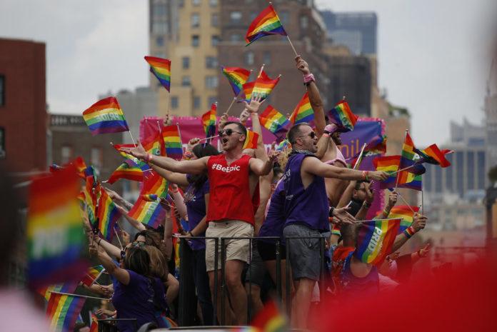 Grupa ludzi z tęczowymi flagami na platformie