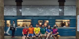 Grupa ludzi ubrana w kolorowe koszulki układające się w tęcze