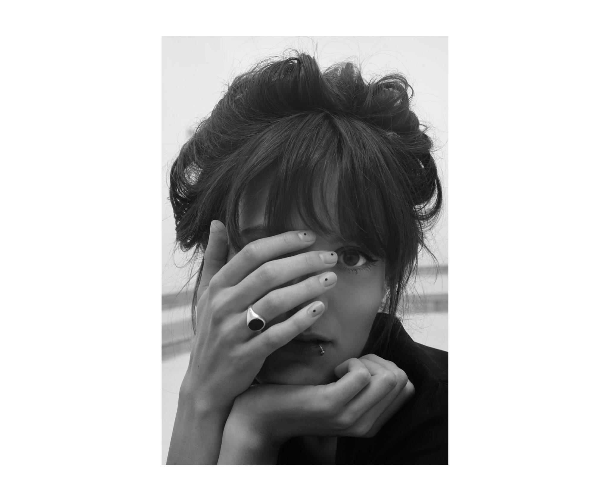 Na czarnobialym zdjeciu widzimy portret mlodej kobiety zakrywajaca dlonia twarz