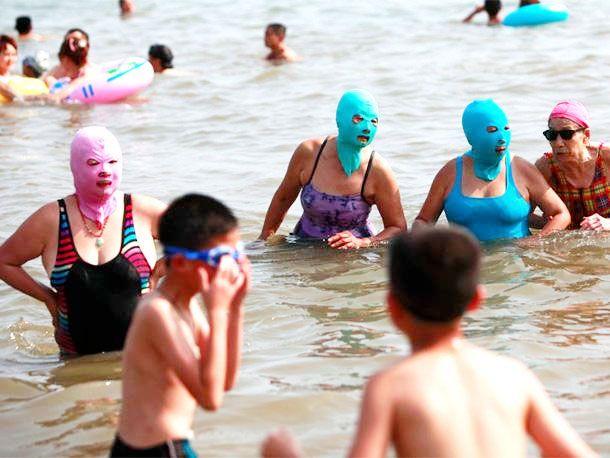 Ludzie w maskach zakrywających twarz siedzący na plazy