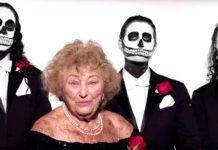 Starsza kobieta w eleganckiej sukni i mężczyźni z pomalowanymi na kościotrupy twarzami