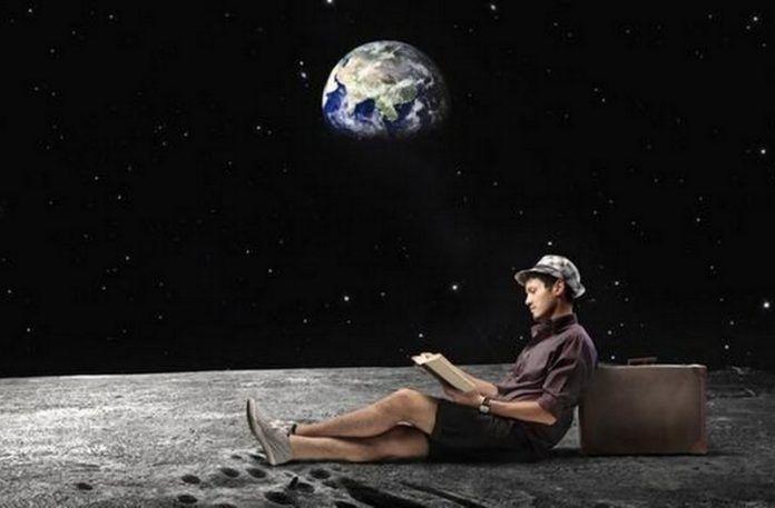 Mężczyzna siedzący wygodnie na innej planecie z widokiem na ziemię