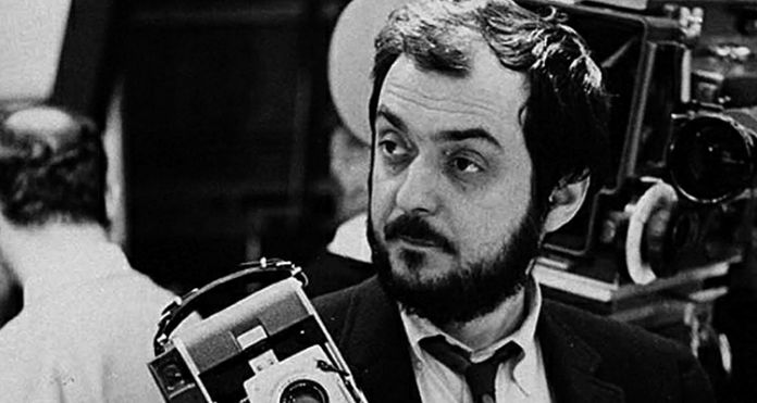 Czarno-białe zdjęcie mężczyzny z zarostem, trzymającym w dłoni kamerę