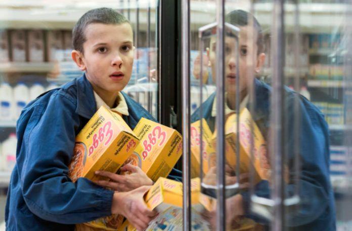 Dziewczyna trzymająca dużo pudełek z mrożonymi goframi