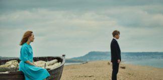 Kobieta siedząca w niebieskiej sukience na łódce i chłopak w garniturze patrzący przed siebie