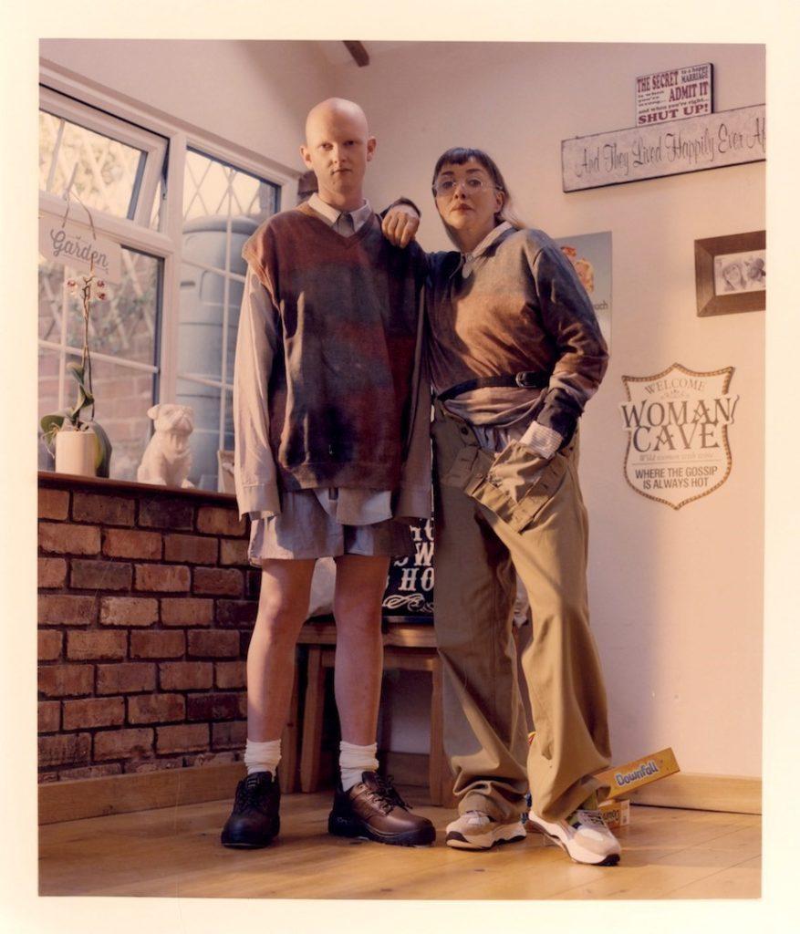 młody mężczyzna i młoda kobita stoją oparci o siebie w pokoju, ubrani są w powyciągane i zniszczone rzeczy