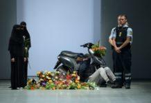 Policjanci i kobiety w niqabie obok skutera i kwiatów na wybiegu