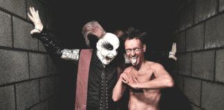 Muzycy niemieckiego zespołu Das Ich w kostiumach. Jeden przebrany za diabła z korpusem pomalowanym na czerwono, drugi jako ksiądz ze stułą z białą twarzą i czerwonymi rogami