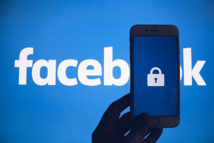 Logotyp Facebook, i ręka trzymająca telefon z kłódką na ekranie