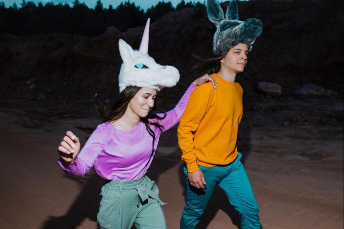 Na zdjeciu widzimy pare chlopaka i dziewczyny biegnacych po lesie ona ma na sobie czapke z jednorozcem a on z oslem