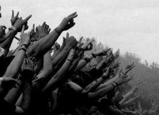 Czarno-białe zdjęcie wyciągniętych rąk podczas koncertu