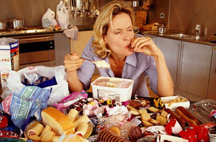 Kobieta siedząca przy stole pełnym jedzenia