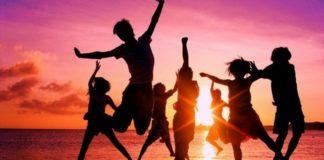 Ludzie skaczący na plaży przy zachodzie słońca