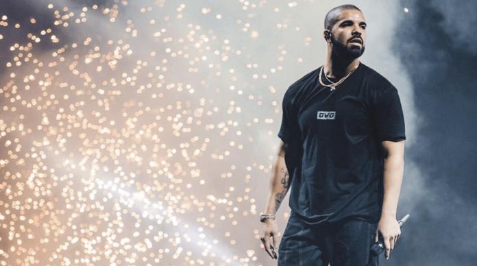 piosenkarz Drake stoi na scenie, za nim iskry