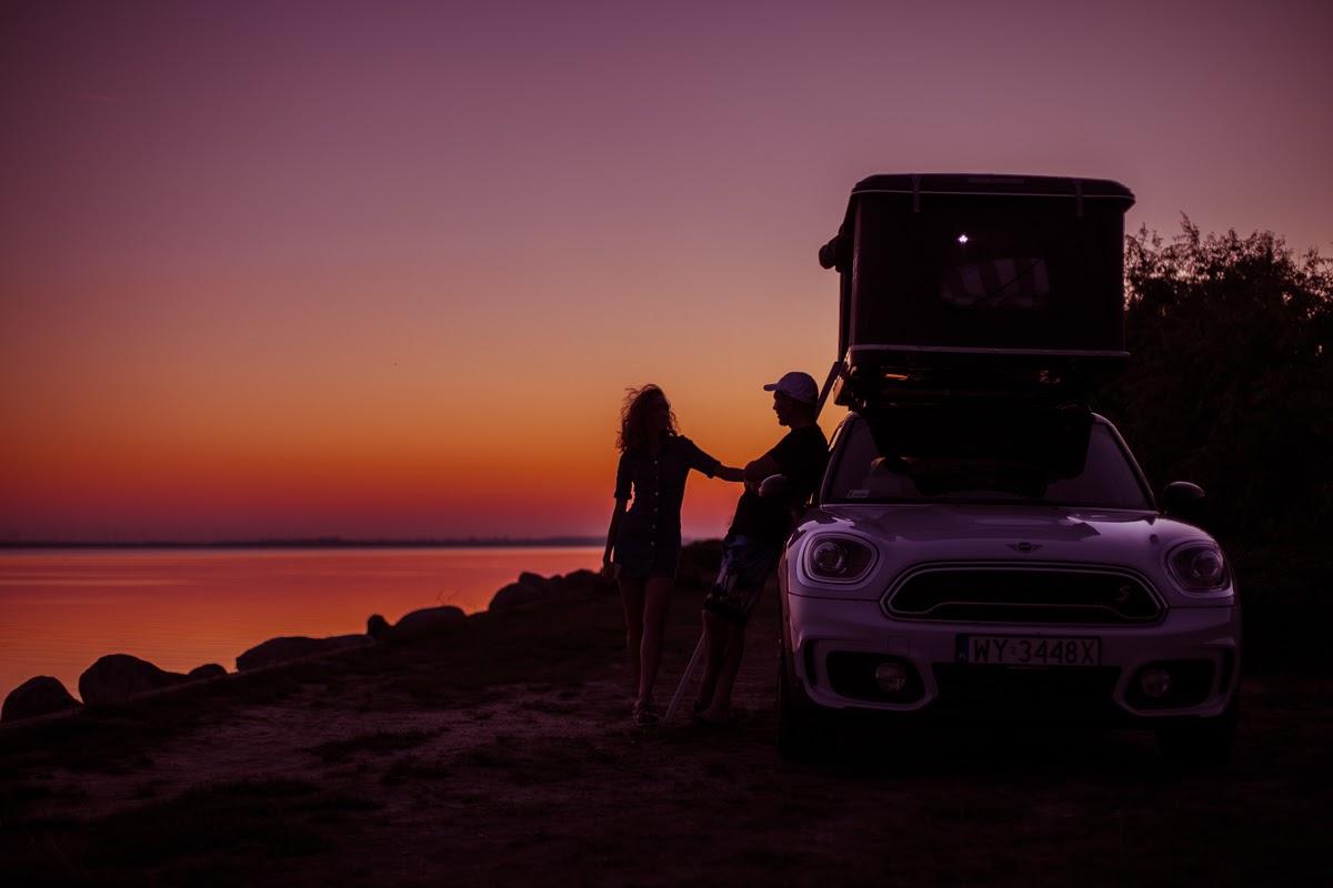 Zachód słońca, samochód z namiotem, męczyzna opiera się o samochód, kobieta stoi obok niego