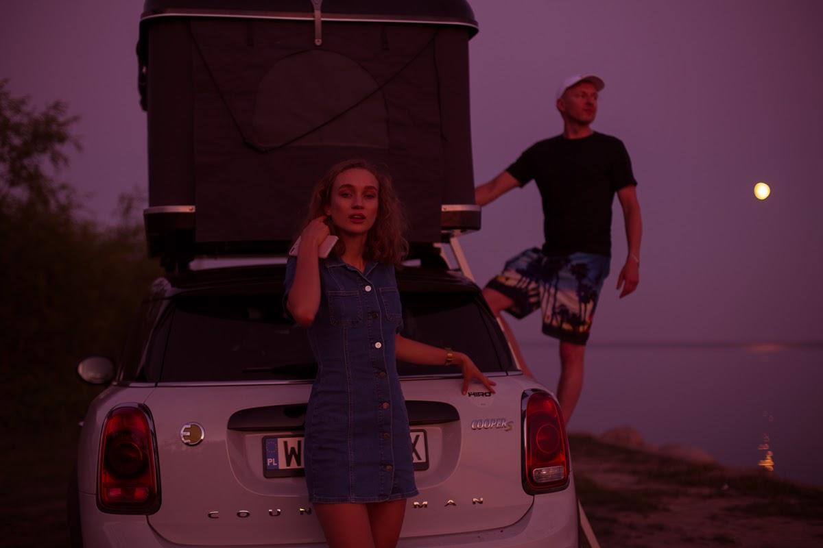 Samochód z namiotem na dachu, dziewczyna w jeansowej sukience i mężczyzna z boku samochodu