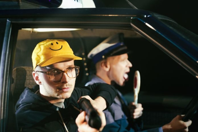 Chłopak w żółtej czapce w uśmiechem, obok męzczyzna w mundurze policyjnym z lizakiem policyjnym