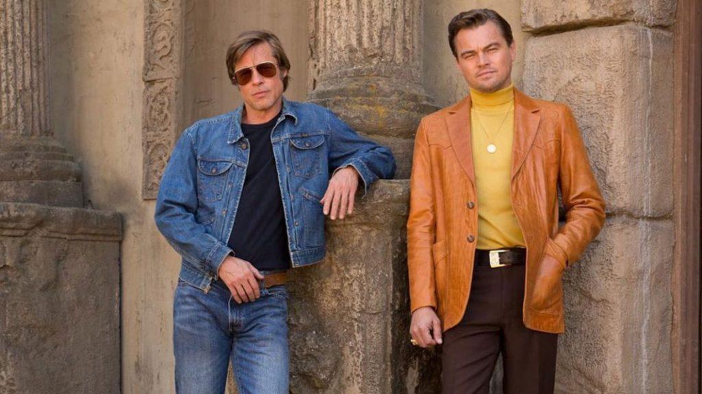 po lewej Brad pitt ubrany w jeansową kurtkę i okulary przeciw słoneczne, po prawej Leonardo Di Caprio w skórzanej kurtce i żółtym golfie