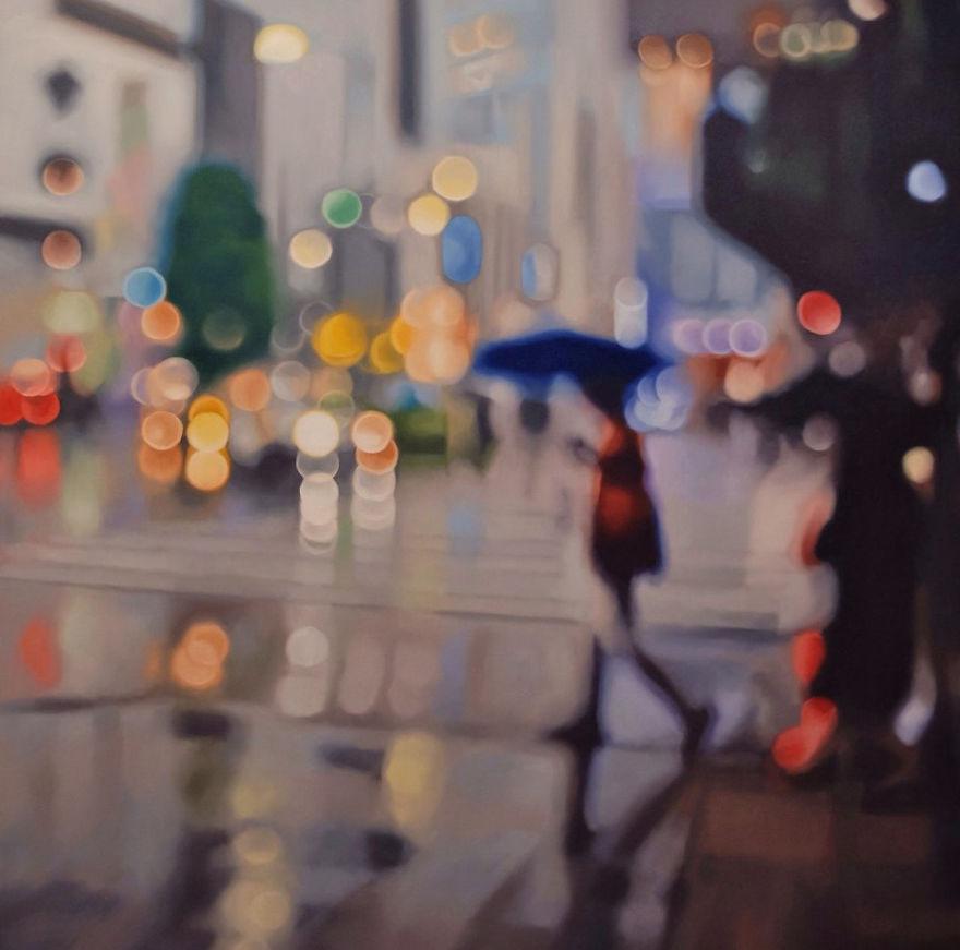 obraz sprawiający wrażenie nieostrego zdjęcia przedstawiający kobietę z parasolką w deszczu w mieście