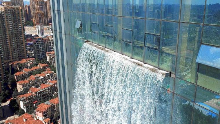 Sztuczny wodospad wypływający z wieżowca w Chinach, widok na spływającą w dół wodę znad miejsca wypływania