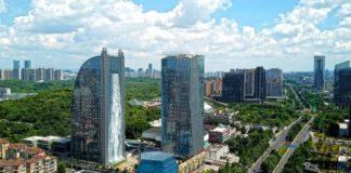 Sztuczny wodospad wypływający z wieżowca w Chinach, widok z panoramą dzielnicy
