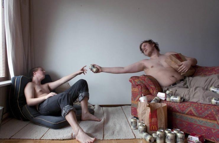Mężczyna podający drugiemu puszkę piwa