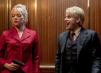 Kobieta w czerwonej garsonce z bronią w dłoni obok i meżczyzna w garniturze