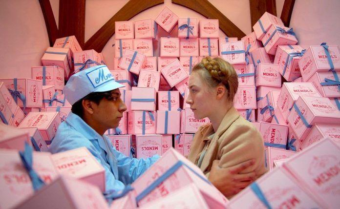 Kobieta i mężczyzna stojący pomiędzy stosem kartonowych różowych pudełek
