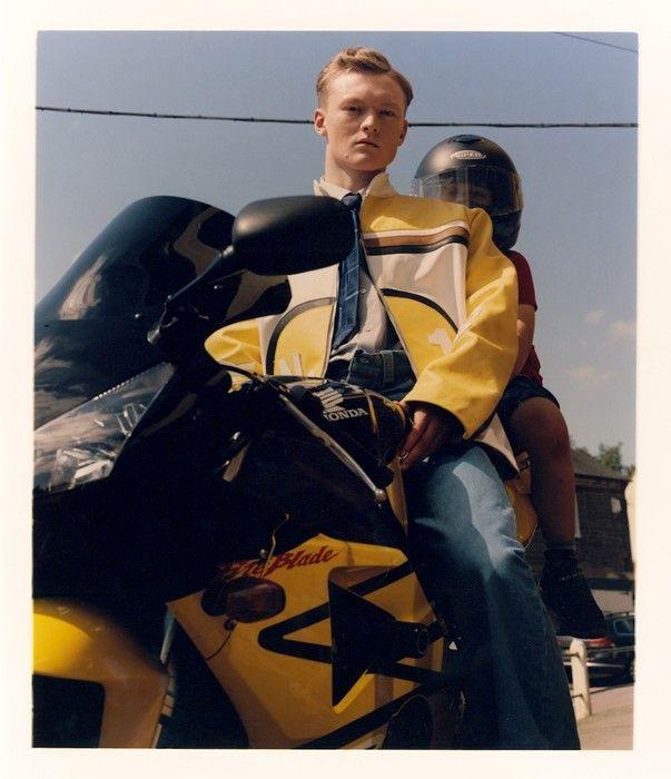 młody mężczyzna siedzi na żółtym motorze w skórzanej kurtce, za nim siedzi młody chłopiec w kasku