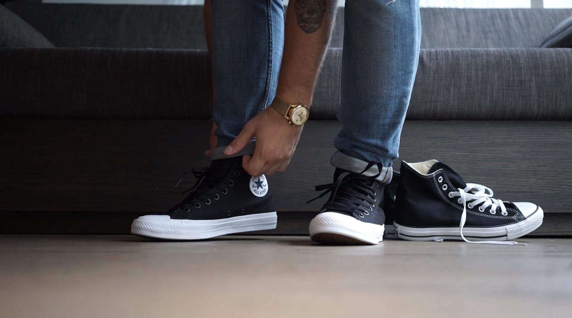 mężczyzna zakładający czarne buty converse