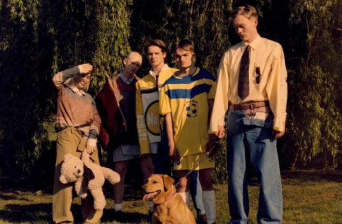 pięciu modeli stoi w ogrodzie z psem, są ubrani w stylu lat 90-tych