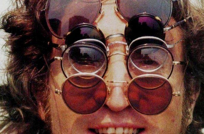 John Lennon w długich włosach z pięcioma parami okularów typu lenonki