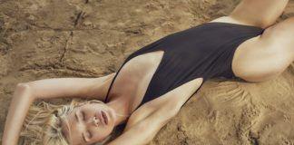 Dziewczyna w czarnym kostiumie leżąca na piasku