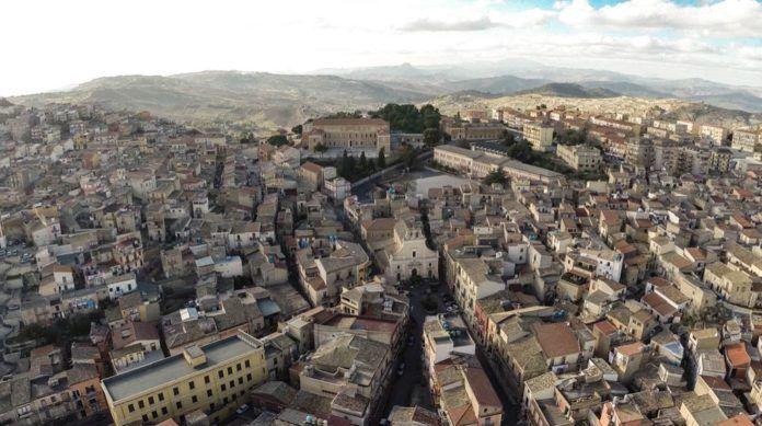 widok na miejscowosc Mussomeli na Sycylii z budynkami o starej wloskiej architekturze w kolorach brazu jasnego i zoltego