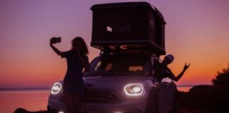 Samochód z namiotem podczas zachodu słońca, przed maską stoi dziewczyna robiąca selfie, w samochodzie wychyla się kierowca przez okno