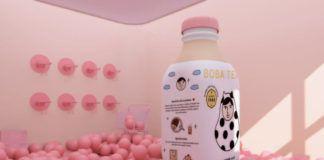 Różowy pokój wypełniony różowymi piłkami i duża butelka