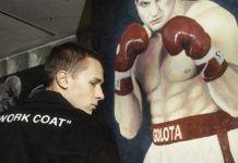 Chłopak w czarnej bluzie na tle plakatu z bokserem