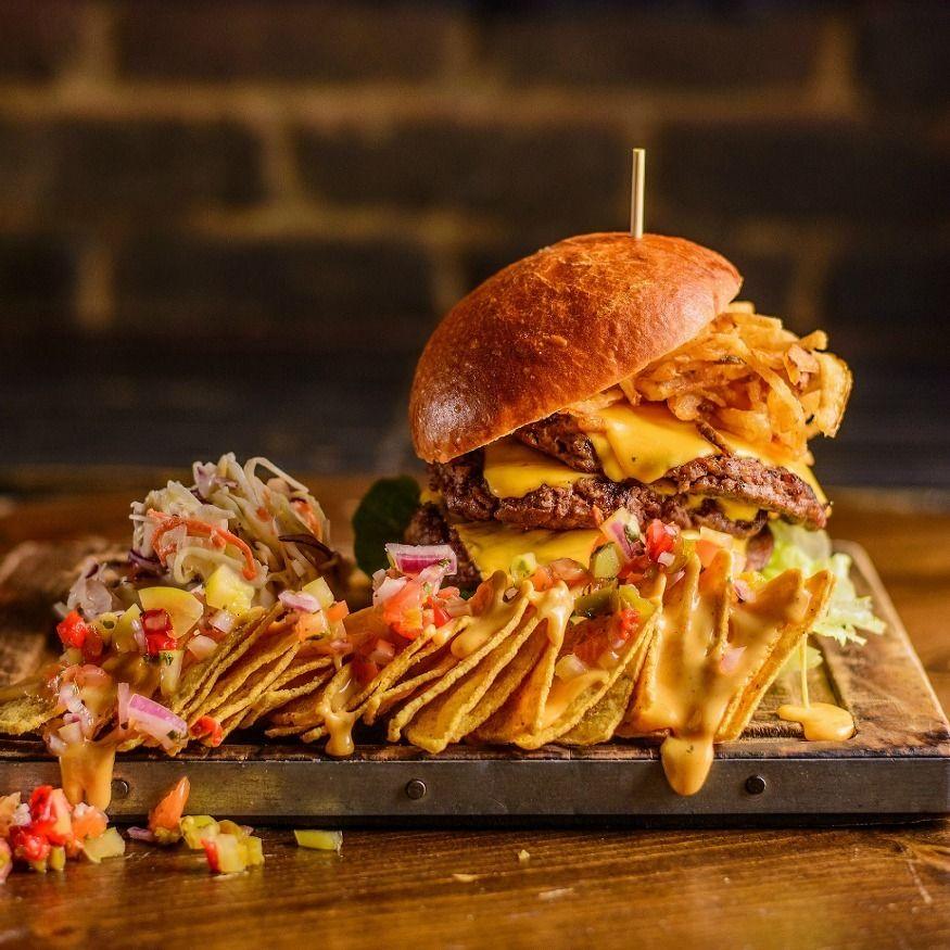 Kolorowe zdjęcie jedzenia fast food - burger, ociekające sosem nachosy i warzywa podane na drewnianej desce na tle ściany z cegieł