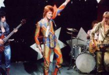 Trzy osoby na scenie, ubrane kolorowo