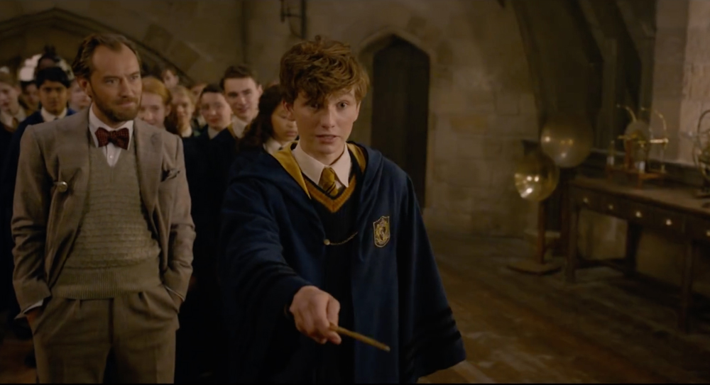 młody newt scamander w szacie hufflepuffu, w tle młody albus dumbledore