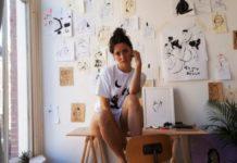 Na zdjeciu widzimy mloda kobiete siedzaca w swojej pracowni artystycznej pelnej szkicow i rysunkow