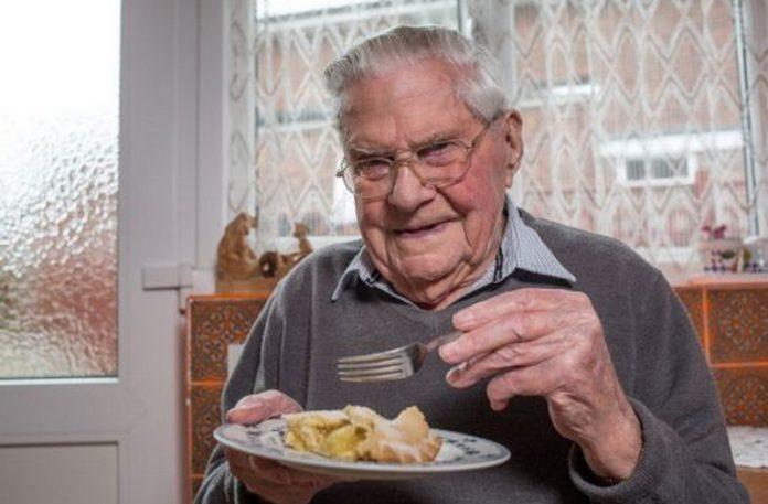 Starszy mężczyzna z ciastem w ręku