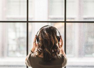 Dziewczyna stojąca tyłem do obiektywu ze słuchawkami na uszach