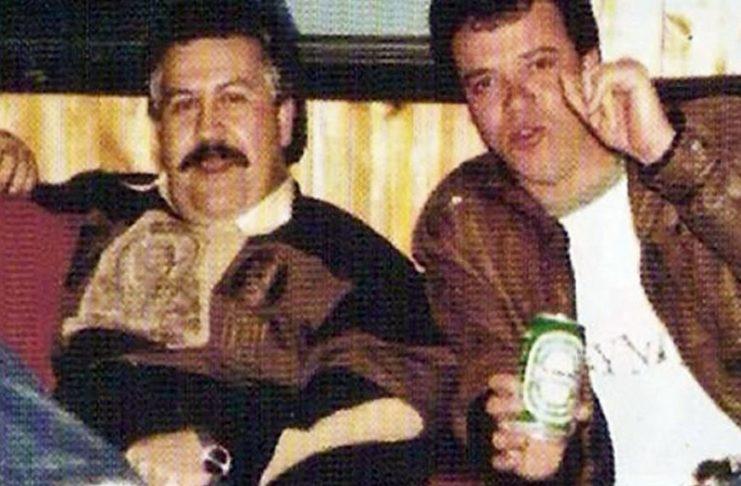 Mężczyzna z wąsem i mężczyzna trzymający puszkę z piwem siedzą na kanapie