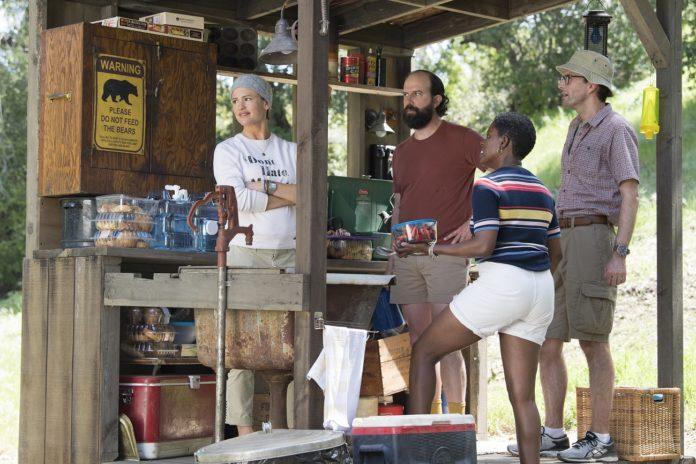 Kilka osób stojących przy drewnianym domku