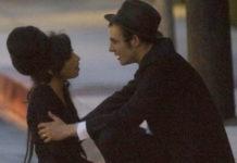 Dziewczyna siedząca na krawężniku i chłopak trzymający ją za ramię