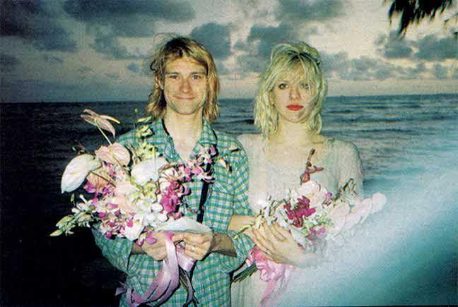 Mężczyzna w piżamie i kobieta w sukience trzymający kwiaty i stojący na tle morza