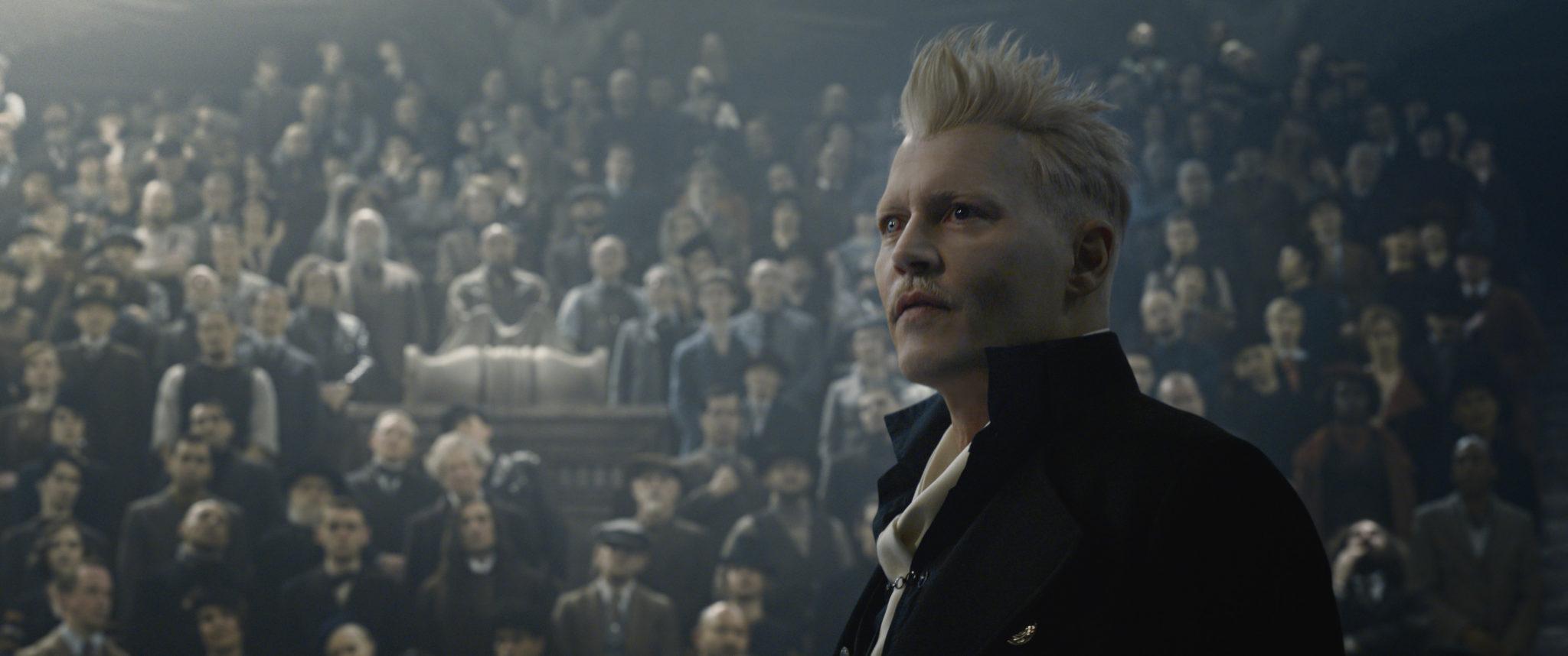 gellert grindelwald stojący na tle tłumu, blond włosy postawione do góry