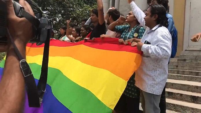 Ludzie trzymający tęczową flagę